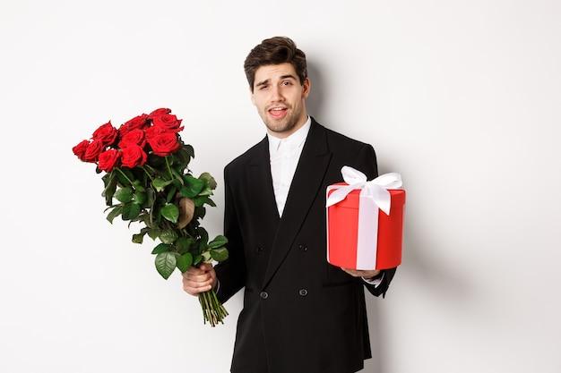 Concept de vacances, de relation et de célébration. bel homme confiant en costume noir, allant à un rendez-vous, tenant un bouquet de roses et présent, debout sur fond blanc