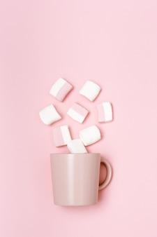 Concept de vacances romantiques, tasse ou tasse rose et guimauves, image monochrome rose pastel, vue de dessus avec espace de copie
