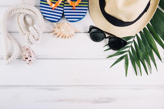 Concept de vacances de vacances d'été. accessoires pour voyager sur une table en bois blanche. vue de dessus et pose à plat