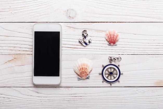 Concept de vacances voyage avec accessoires de mer, smartphone, coquillages. vue de dessus avec espace de copie