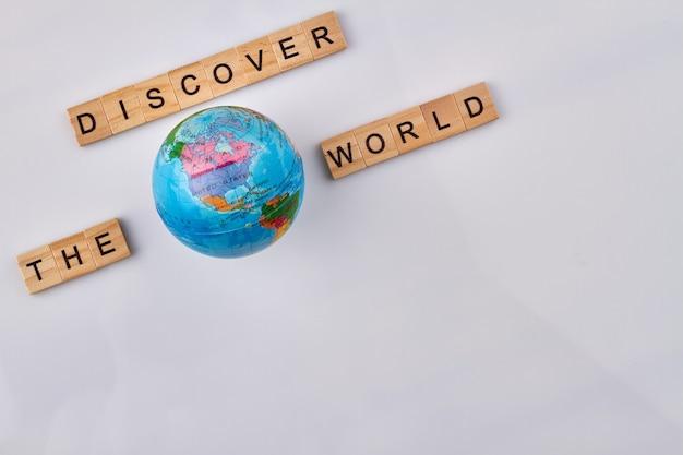 Concept de vacances de voyage. cubes en bois alphabet et globe sur fond blanc. découvrez le monde fait de blocs de lettres.