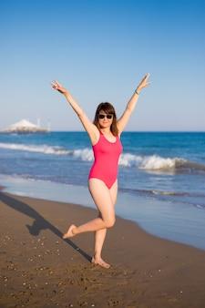Concept de vacances et de voyage d'été - portrait en pied d'une belle jeune femme joyeuse en maillot de bain rose à la plage