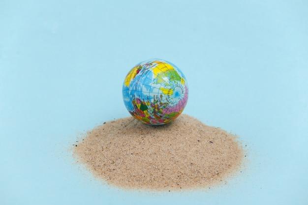 Concept de vacances de voyage de plage d'été. globe sur une île de sable