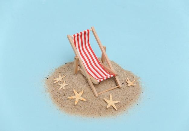 Concept de vacances de voyage de plage d'été. mini chaise longue de plage sur l'île avec du sable et des étoiles de mer