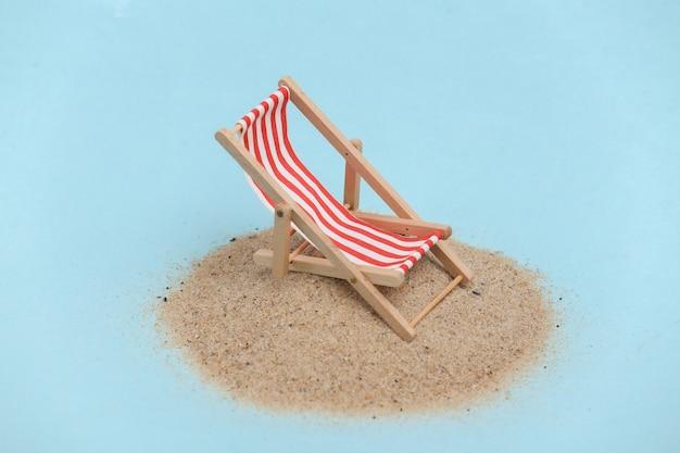 Concept de vacances de voyage de plage d'été. mini chaise longue de plage sur une île de sable