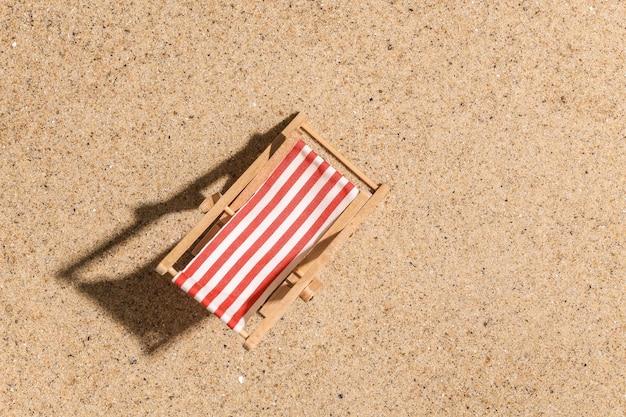 Concept de vacances de voyage de plage d'été. mini chaise longue de plage sur le sable en journée ensoleillée. vue de dessus