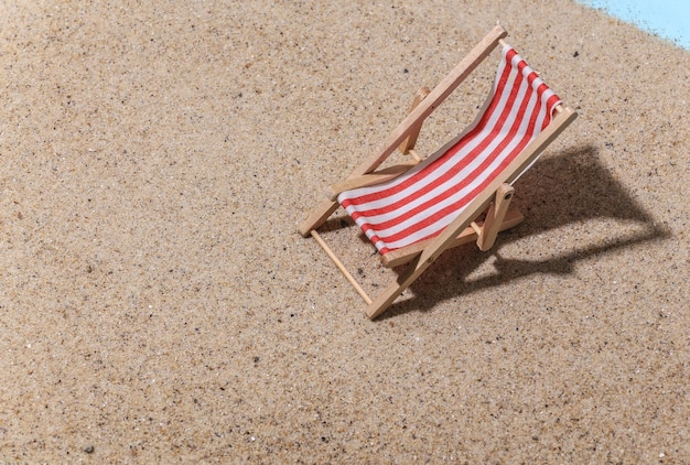 Concept de vacances de voyage de plage d'été. mini chaise longue de plage sur le sable en journée ensoleillée.