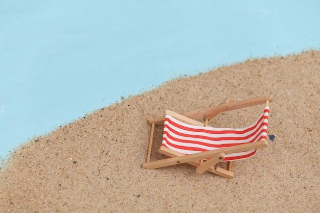 Concept de vacances de voyage de plage d'été. mini chaise longue de plage sur le sable