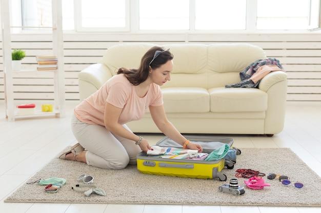 Concept de vacances, voyage et voyage - femme recueille une valise jaune à la maison