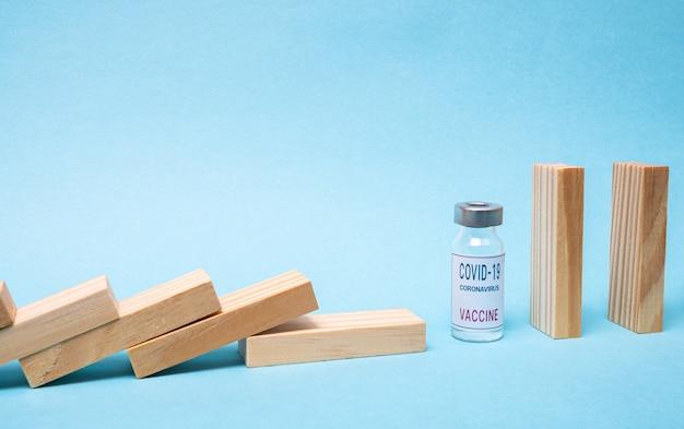 Concept de vaccin avec domino bois et ampoule de vaccin covid-19 sur fond bleu.