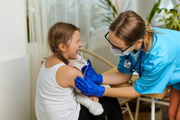 Le concept de vaccination. femme médecin vaccinant mignonne petite fille en clinique