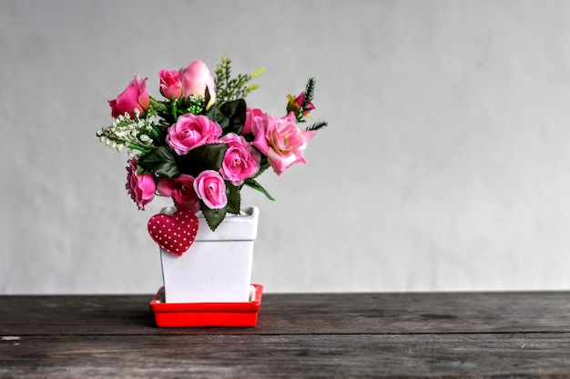 Concept valentine, les fleurs roses roses sont dans un pot en céramique blanche sur une table en bois.