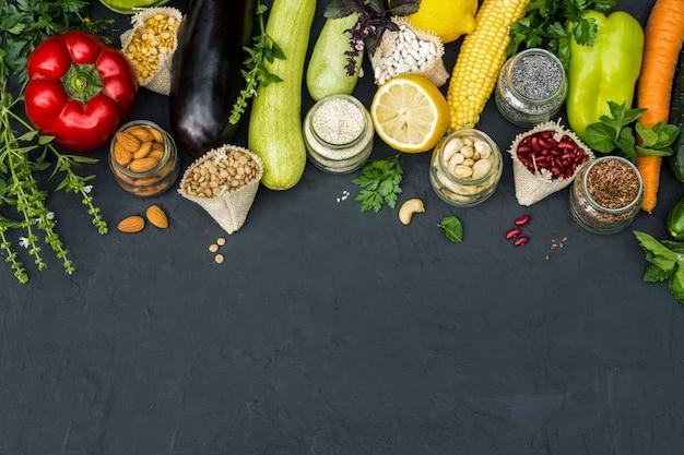 Concept végétarien légumes noix et céréales sur fond noir.