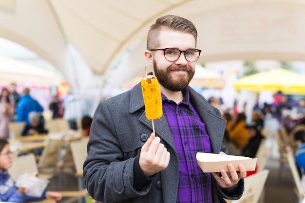 Concept végétarien et repas - bel homme mangeant du maïs de rue au festival de restauration rapide