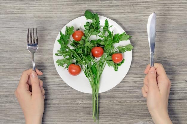 Concept de végétarisme. tio voir la photo des mains et de l'assiette de wonam avec des tomates cerises et du persil sur une table en bois