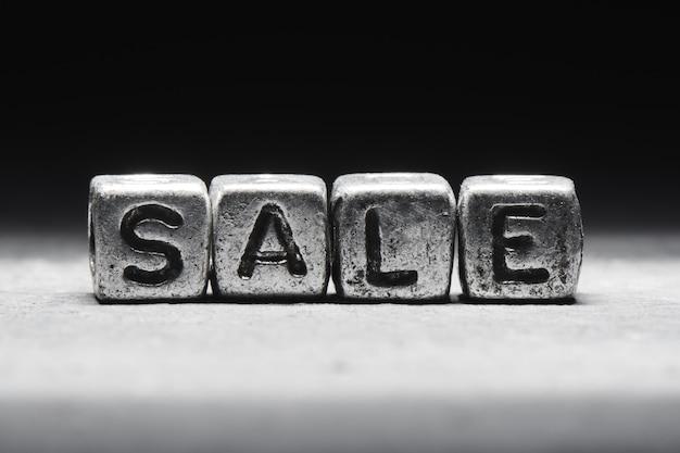 Le concept de à vendre. l'inscription sur des cubes 3d métalliques isolés sur fond noir, style grunge