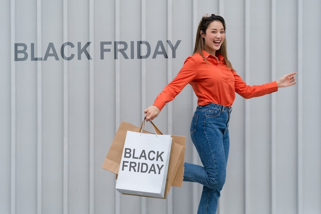 Concept de vendredi noir, femme tenant de nombreux sacs à provisions marchant avec des sacs colorés près du magasin pendant le processus d'achat