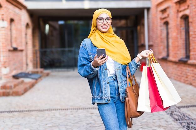 Concept de vente et d'achat - bonne fille musulmane arabe avec des sacs après le centre commercial