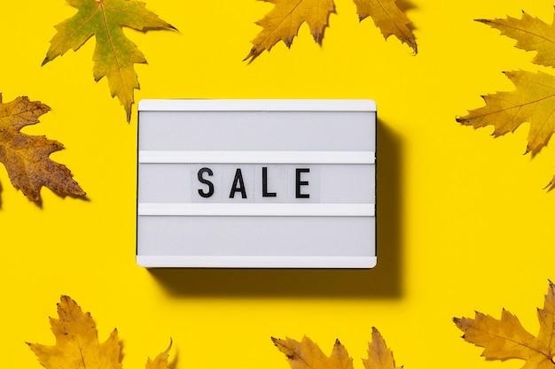 Concept de vente d'automne vente de texte sur fond jaune vif avec des feuilles d'érable colorées