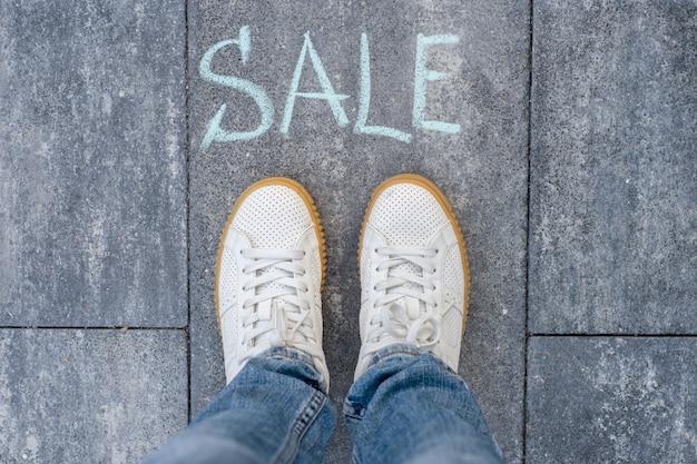 Concept de vente à l'avance avec des pieds de femme sur une route goudronnée avec texte