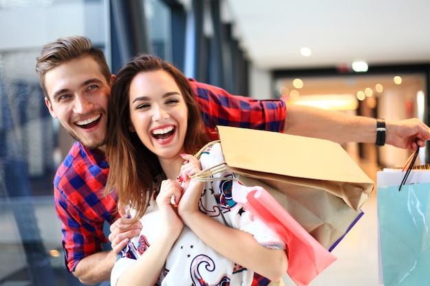 Concept de vente, de consommation et de personnes - heureux jeune couple avec des sacs à provisions marchant dans le centre commercial.