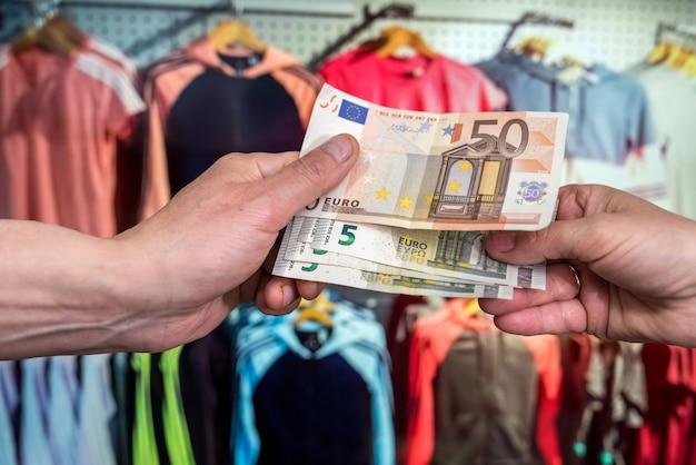 Concept de vente homme donne des billets en euros dans la boutique shopping