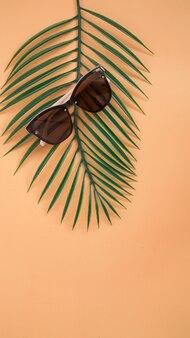 Concept de vente de lunettes de soleil. lunettes de soleil sur fond orange avec des feuilles tropicales. accessoires d'été à la mode. vue de dessus, verticale