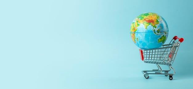 Concept de vente mondiale et de vente sur internet. chariot de supermarché avec globe terrestre sur fond bleu. commerce mondial et livraison des achats