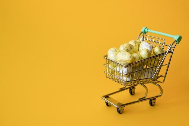 Concept de vente de pâques. oeufs de pâques jaunes dans un petit caddie sur jaune.