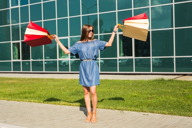 Concept de vente, de shopping et de gens heureux - belle femme avec des sacs à provisions marchant dans une rue.