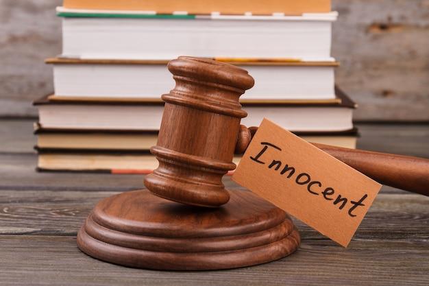 Concept de verdict innocent. marteau de cour en bois et pile de livres.