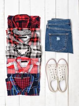 Concept de vêtements. chemises à carreaux, jeans bleus et baskets blanches sur un fond en bois blanc. vue de dessus