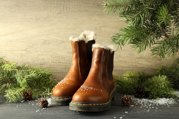 Concept de vêtements d'hiver avec des bottes sur une table en bois sombre.