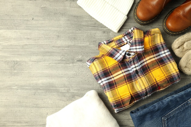 Concept de vêtements d'hiver sur table en bois gris.