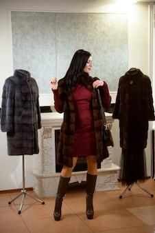 Concept de vêtements de luxe. femme avec manteau de fourrure. fille dans un manteau de fourrure en magasin avec de la fourrure sur l'arrière-plan.