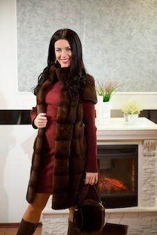 Concept de vêtements de luxe. femme avec manteau de fourrure. fille dans un manteau de manteau de fourrure en boutique avec fourrure sur fond.