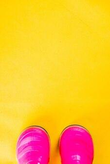 Concept de vêtements pour enfants automne, bottes en caoutchouc rose vif pour la pluie