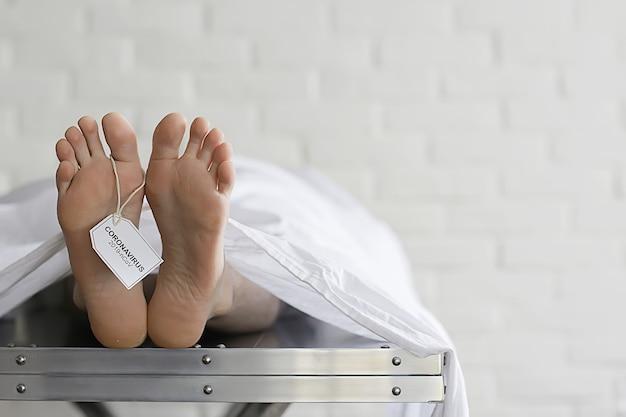 Concept victime d'un coronavirus d'imitation de morgue tuée par 2019ncov les jambes d'un cadavre sur une table, un homme est décédé