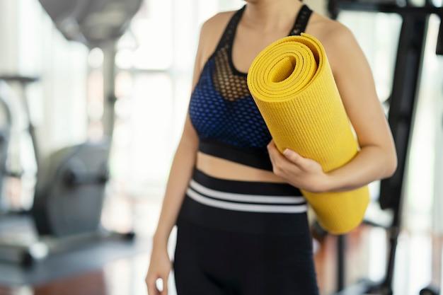 Concept de vie en bonne santé. jeune femme tenant un tapis de yoga jaune, entraînement dynamique en cours de yoga