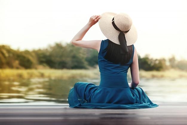 Concept de vie et de relaxation débranché. portrait de jeune femme relaxante au bord du fleuve. assis sur une terrasse en bois et regarder ailleurs
