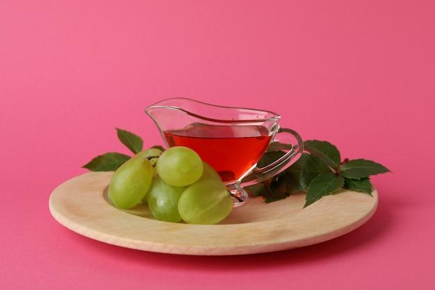 Concept de vinaigre de raisin sur fond rose