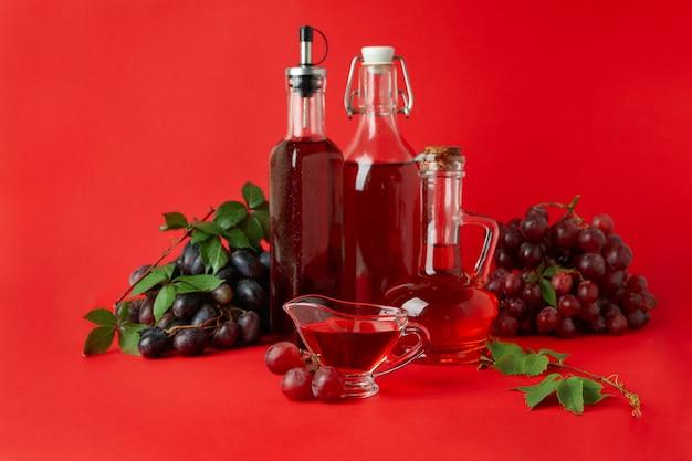 Concept de vinaigre de raisin sur fond rouge