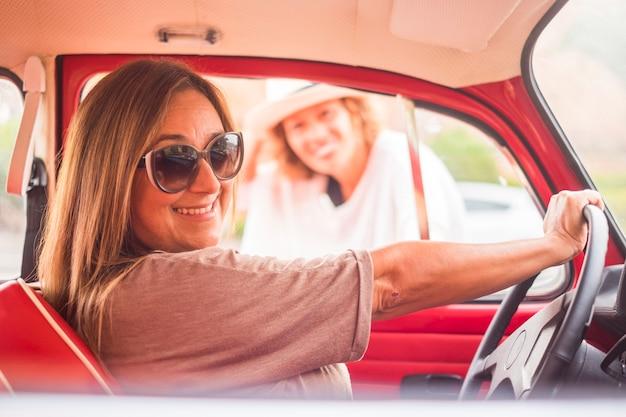 Concept vintage et rétro avec deux femmes en amitié avec une voiture légendaire rouge. concept de liberté et de mode de vie alternatif
