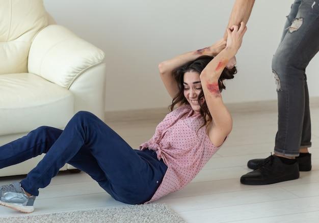 Concept de violence domestique, d'alcoolisme et d'abus - homme agressif attrapant sa femme allongée sur le sol.