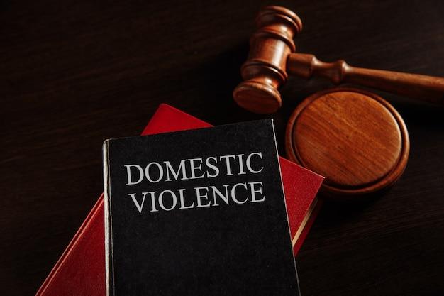 Concept de violence domestique. marteau en bois sur le gros livre rouge