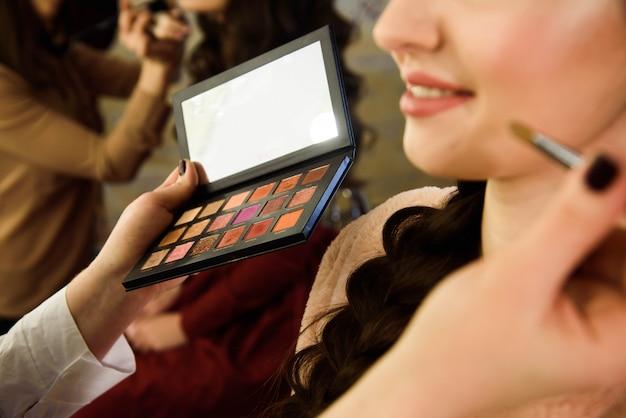 Concept de visage. gros plan femme se maquiller sur les paupières. appliquer un fard à paupières avec un pinceau par un artiste professionnel.