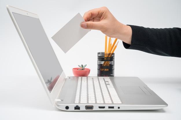Concept de vote en ligne avec un homme avec un bulletin de vote à la main mettant un bulletin de vote vers l'écran de l'ordinateur.
