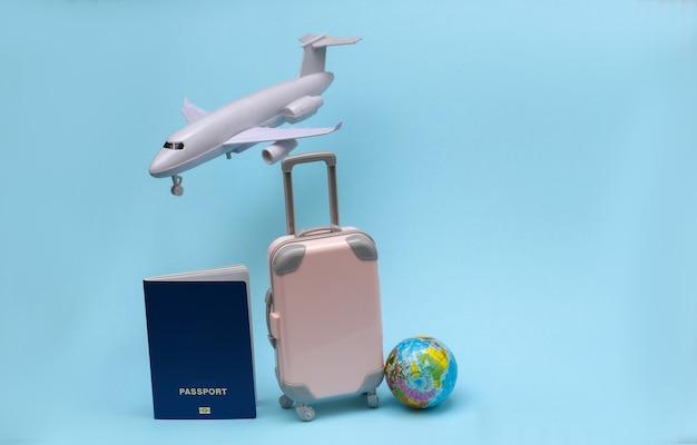 Concept de voyage aérien. mini valise de voyage, avion, globe, passeport sur fond bleu pastel.
