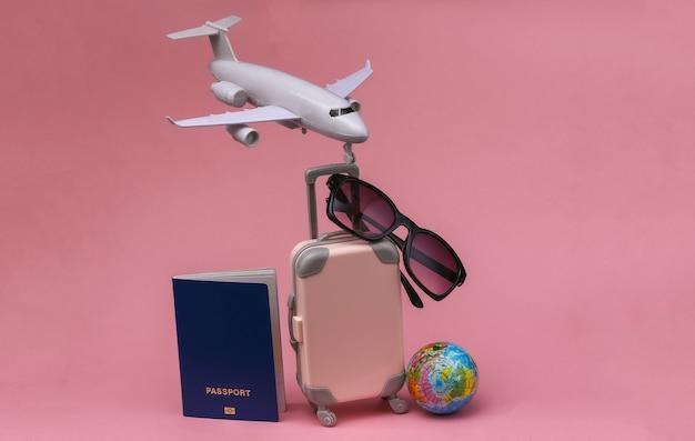 Concept de voyage aérien. mini valise de voyage, avion, globe, passeport et lunettes de soleil sur fond pastel rose.