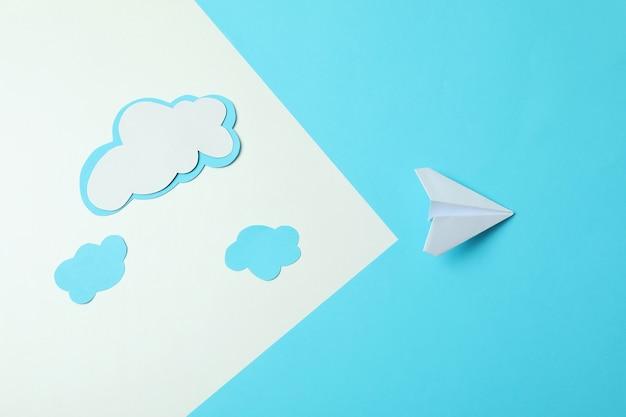 Concept de voyage avec avion en papier et nuages sur fond de deux tons